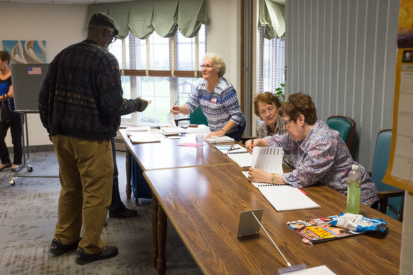 JOED VIERA/STAFF PHOTOGRAPHER-Lockport, NY-Virgil Lee Humphrey asks Christine Kennedy for a replacement ballot as Gail Montedoro and Diane McNall look through registration lists for his name at Briarwood Manor.