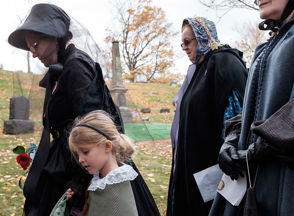 JOED VIERA/STAFF PHOTOGRAPHER-Lockport, NY-  Claudia Carnes carries a rose while walking with her granddaughter Hailey Carnes, 5, Susan Berardi and Donna Schmidt before the unveiling ceremony for the Whitcher Monument.