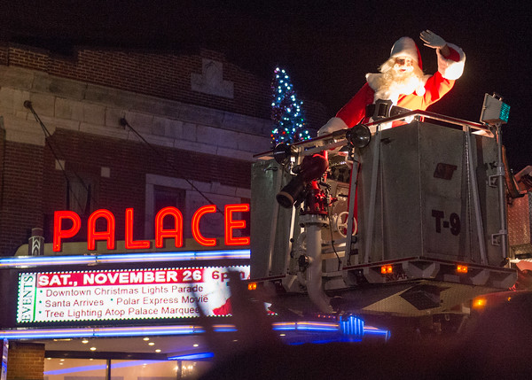 JOED VIERA/STAFF PHOTOGRAPHER-Lockport, NY-   Santa Clauss waves while riding atop a Lockport Fire Engine after lighting up a Lockport Christmas tree during the parade in front of the Palace Theatre.