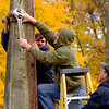 JOED VIERA/STAFF PHOTOGRAPHER-Lockport, NY-Ben Insalaco holds a clamp Nick Mastropoll is removing with a wrench as Edward Ives stablizes Mastropoll's ladder while working to re-erect the Whitcher monument Wednesday afternoon.