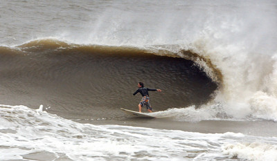 A surfer catches a large wave at the Poles, Saturday Oct. 27, 2012 in Jacksonville, Fla. Hurricane Sandy, upgraded again Saturday just hours after forecasters said it had weakened to a tropical storm, was barreling north from the Caribbean and was expected to make landfall early Tuesday near the Delaware coast, then hit two winter weather systems as it moves inland, creating a hybrid monster storm.   (AP Photo/The Florida Times-Union, Bob Mack)