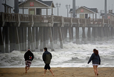 Beachgoers walk in the wind and rain as waves generated by Hurricane Sandy crash into Jeanette's Pier in Nags Head, N.C., Saturday, Oct. 27, 2012 as the storm churns up the east coast. Hurricane Sandy, upgraded again Saturday just hours after forecasters said it had weakened to a tropical storm, was barreling north from the Caribbean and was expected to make landfall early Tuesday near the Delaware coast, then hit two winter weather systems as it moves inland, creating a hybrid monster storm. (AP Photo/Gerry Broome)
