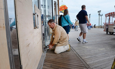 Bally's employee Frank Jiacopello of Dorothy N.J. affixes plywood on the doors and windows at Bally's Atlantic City along the boardwalk as patrons enter and exit the casino,Saturday Oct. 27 2012 in Atlantic City, N.J.. With Hurricane Sandy taking aim at New Jersey, Gov. Chris Christie ordered Atlantic City's 12 casinos to shut down at 4 p.m. Sunday as part of his statewide emergency declaration. (AP Photo/The Press of Atlantic City, Ben Fogletto) MANDATORY CREDIT