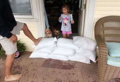 Hannah Smith, 4, looks over a pile of sandbags as her dad, Charles, checks their stability in front of their home along Ocean View Avenue Saturday, Oct. 27, 2012 in Norfolk, Va. Hurricane Sandy, upgraded again Saturday just hours after forecasters said it had weakened to a tropical storm, was barreling north from the Caribbean and was expected to make landfall early Tuesday near the Delaware coast, then hit two winter weather systems as it moves inland, creating a hybrid monster storm. (AP Photo/The Virginian-Pilot, Ross Taylor)  MAGS OUT