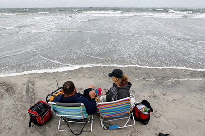 George Barats, of Levittown, Pa., and Michele Scheid, of Bristol, Pa., sit on the edge of a churning Atlantic Ocean Saturday, Oct. 27, 2012, in North Wildwood, N.J., as Hurricane Sandy begins to show its effects. From the lowest lying areas of the Jersey shore, where residents were already being encouraged to leave, to the state's northern highlands, where sandbags were being filled and cars moved into parking lots on high ground, New Jersey began preparing in earnest for Hurricane Sandy. (AP Photo/Mel Evans)