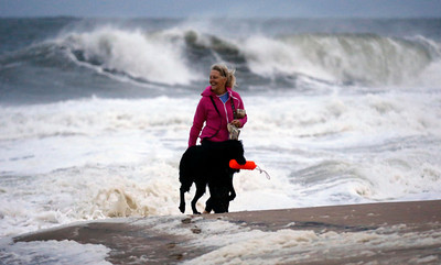 "Annemarie Jarman, and her dog ""Bruges,"" walk along the edge of the beach that is mostly empty as Hurricane Sandy bears down on the east coast, Saturday, Oct. 27, 2012, in Ocean City, Md. Hurricane Sandy, upgraded again Saturday just hours after forecasters said it had weakened to a tropical storm, was barreling north from the Caribbean and was expected to make landfall early Tuesday near the Delaware coast, then hit two winter weather systems as it moves inland, creating a hybrid monster storm. (AP Photo/Alex Brandon)"