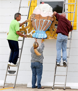 Richard Caguilat, left, William Disburger, right, and Carol Seymour remove a large sign from the Sea Shell Ice Cream shop in Wildwood, N.J., Saturday, Oct. 27, 2012, in preparation for Hurricane Sandy. From the lowest lying areas of the Jersey shore, where residents were already being encouraged to leave, to the state's northern highlands, where sandbags were being filled and cars moved into parking lots on high ground, New Jersey began preparing in earnest for Hurricane Sandy. (AP Photo/Mel Evans)