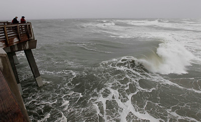 Huge waves crash as onlookers peer from Jeanette's Pier in Nags Head, N.C.,  as Hurricane Sandy churns up the east coast  Saturday, Oct. 27, 2012. Hurricane Sandy, upgraded again Saturday just hours after forecasters said it had weakened to a tropical storm, was barreling north from the Caribbean and was expected to make landfall early Tuesday near the Delaware coast, then hit two winter weather systems as it moves inland, creating a hybrid monster storm. (AP Photo/Gerry Broome)