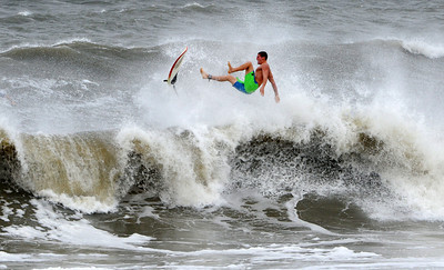 A surfer kicks out at the top of a wave after a ride, Saturday Oct. 27, 2012 in Jacksonville, Fla. Hurricane Sandy, upgraded again Saturday just hours after forecasters said it had weakened to a tropical storm, was barreling north from the Caribbean and was expected to make landfall early Tuesday near the Delaware coast, then hit two winter weather systems as it moves inland, creating a hybrid monster storm.   (AP Photo/The Florida Times-Union, Bob Mack)