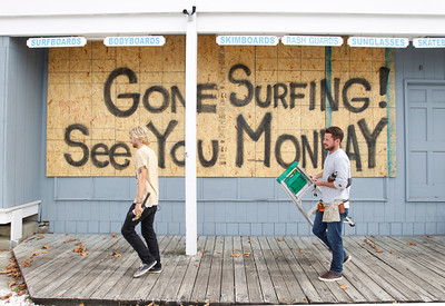 Store workers Fletcher Birch, right, and Jay Kleman finish boarding up the windows on a surf store in Ocean City, Md. on Saturday, Oct. 27, 2012 as Hurricane Sandy approaches the Atlantic coast. (AP Photo/Jose Luis Magana)