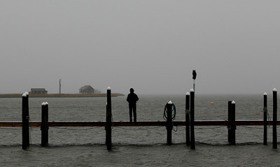 Corissa Martinez looks out over the Pamlico Sound in Nags Head, N.C., Saturday, Oct. 27, 2012 as Hurricane Sandy churns up the east coast. Hurricane Sandy, upgraded again Saturday just hours after forecasters said it had weakened to a tropical storm, was barreling north from the Caribbean and was expected to make landfall early Tuesday near the Delaware coast, then hit two winter weather systems as it moves inland, creating a hybrid monster storm. (AP Photo/Gerry Broome)