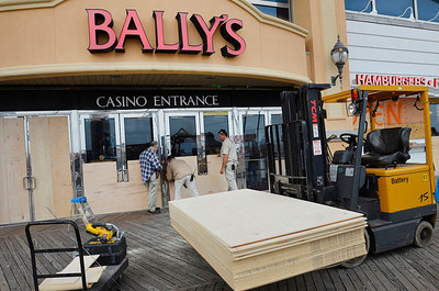 Bally's crews board doors and windows at Bally's Atlantic City along the boardwalk, Saturday Oct. 27 2012 in Atlantic City, N.J.. With Hurricane Sandy taking aim at New Jersey, Gov. Chris Christie ordered Atlantic City's 12 casinos to shut down at 4 p.m. Sunday as part of his statewide emergency declaration. (AP Photo/The Press of Atlantic City, Ben Fogletto) MANDATORY CREDIT