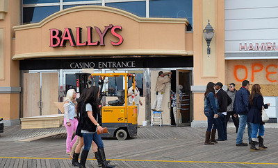 Bally's crews affix plywood on the doors and windows at Bally's Atlantic City along the boardwalk as patrons enter and exit the casino, Saturday Oct. 27 2012 in Atlantic City, N.J.. With Hurricane Sandy taking aim at New Jersey, Gov. Chris Christie ordered Atlantic City's 12 casinos to shut down at 4 p.m. Sunday as part of his statewide emergency declaration. (AP Photo/The Press of Atlantic City, Ben Fogletto) MANDATORY CREDIT