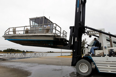 A marina worker uses a forklift to move a boat at the Indian River Marina in Delaware, Md. on Saturday, Oct. 27, 2012 as Hurricane Sandy approaches the Atlantic coast. ( AP Photo/Jose Luis Magana)