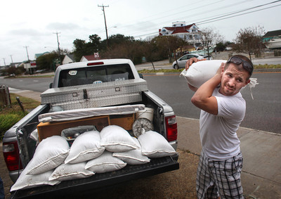Nick Almeter, 26,  prepares for another storm, as he carries another sandbag to place by properties along Ocean View Avenue, Saturday, Oct. 27, 2012 in Norfolk, Va. Hurricane Sandy, upgraded again Saturday just hours after forecasters said it had weakened to a tropical storm, was barreling north from the Caribbean and was expected to make landfall early Tuesday near the Delaware coast, then hit two winter weather systems as it moves inland, creating a hybrid monster storm. (AP Photo/The Virginian-Pilot, Ross Taylor)  MAGS OUT