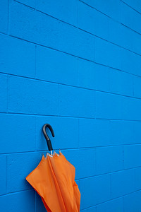 Orange Umbrella Against Blue Wall -- Vertical