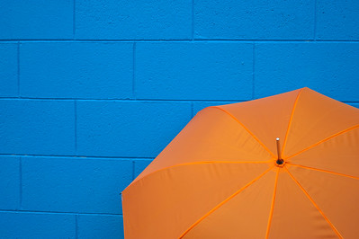 Orange Umbrella Against Blue Wall -- Horizontal