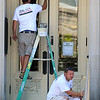 Owner of M & R Painting in Leominster Mike Pompeo paints the door to the Leominster Public Library as his employee Justin Tarbell of Fitchburg paints the rails on Tuesday afternoon. They have been working on the building for the past several weeks. SENTINEL & ENTERPRISE/JOHN LOVE