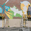 Artist Monique Guthrie, on left, and Erin Cregg got a Community Development Block grant from the City of Fitchburg to paint a mural on the back wall of the Fitchburg Public Library. On Monday Guthrie was painting the Greek god Poseidon and Cregg was painting the Greek god Athena. SENTINEL & ENTERPRISE/JOHN LOVE