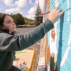 Artists Monique Guthrie, pictured, and Erin Cregg got a Community Development Block grant from the City of Fitchburg to paint a mural on the back wall of the Fitchburg Public Library. On Monday Guthrie, pictured, was painting the Greek god Poseidon and Cregg was painting the Greek god Athena. SENTINEL & ENTERPRISE/JOHN LOVE