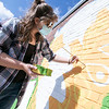 Artists Monique Guthrie and Erin Cregg, pictured, got a Community Development Block grant from the City of Fitchburg to paint a mural on the back wall of the Fitchburg Public Library. On Monday Guthrie was painting the Greek god Poseidon and Cregg was painting the Greek god Athena. SENTINEL & ENTERPRISE/JOHN LOVE