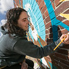 Artist Monique Guthrie, pictured, and Erin Cregg got a Community Development Block grant from the City of Fitchburg to paint a mural on the back wall of the Fitchburg Public Library. On Monday Guthrie was painting the Greek god Poseidon and Cregg was painting the Greek god Athena. SENTINEL & ENTERPRISE/JOHN LOVE