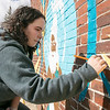 Artists Monique Guthrie, pictured, and Erin Cregg got a Community Development Block grant from the City of Fitchburg to paint a mural on the back wall of the Fitchburg Public Library. On Monday Guthrie was painting the Greek god Poseidon and Cregg was painting the Greek god Athena. SENTINEL & ENTERPRISE/JOHN LOVE