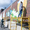 Artists Monique Guthrie, on ground, and Erin Cregg got a Community Development Block grant from the City of Fitchburg to paint a mural on the back wall of the Fitchburg Public Library. On Monday Guthrie was painting the Greek god Poseidon and Cregg was painting the Greek god Athena. SENTINEL & ENTERPRISE/JOHN LOVE