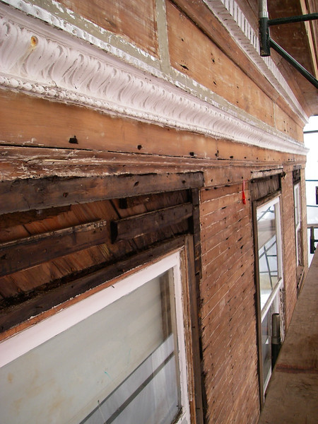 Stripped siding, dry-rot holes. Some trim around windows has been removed prior to installation of new sash.