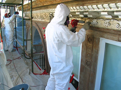 Stripping plaster ornament (and everything else) with heat gun. Note containments and worker protection.
