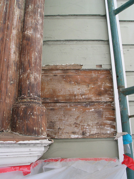 "Close up view existing old alligatored paint and a stripped section.  This facade had been ""worked over"" a couple of times in the past, including damage from a fire. None of the previously performed work was of high quality. You can see old damage and scars in the surfaces that have been stripped."