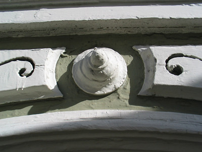 Before photo of ornament above window casing.