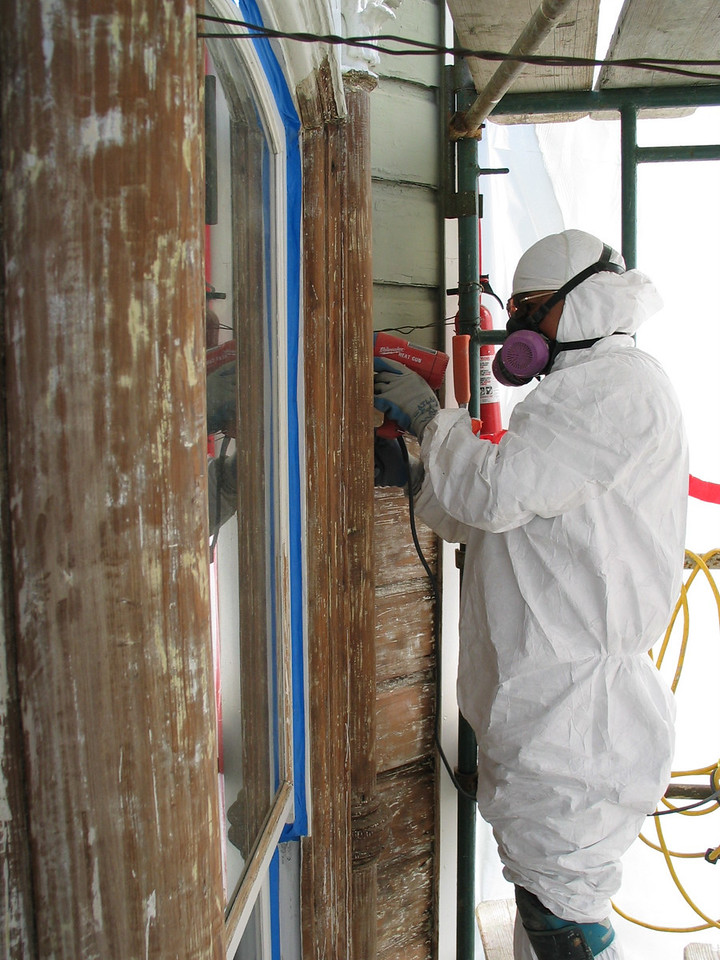 Stripping almost all of the old, lead containing, paint from this facade was required. Note the worker protective gear as well as the fire extinguisher (water hose also a necessity).