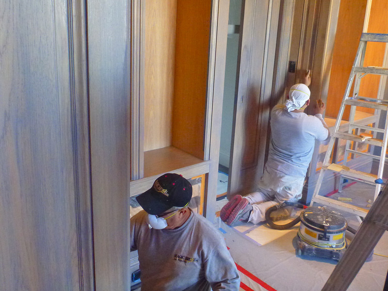 Pacific Avenue Residence, pecan Library panelling, applying stain after stripping. In order to get the color just right, we heavily applied the stain, allowed it to dry, and then sanded most of it off, leaving color down in the pores and molding details.