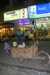 A cart with corn on the cob cooked in sand