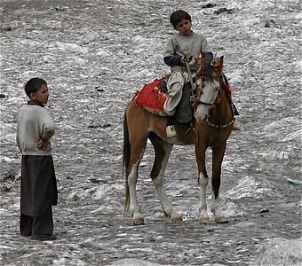 Boy riding horse on one of the glaciers near Lake Saif-Ul-Malook, Pakistan.