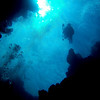Looking up at a solo diver descending from one of the blue holes lit far above.
