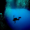 A diver whose silhouette is back-lighted by one of the caverns two exits along the reef wall.