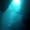Three divers descend into the cavern from one of the Blue Holes at the reef top.