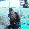I am preparing to begin a dive by a back entry off of the boat.  To do so, I place my hand in front of my face to hold my mask and regulator, as I roll from the boat backwards into the water, tank first.