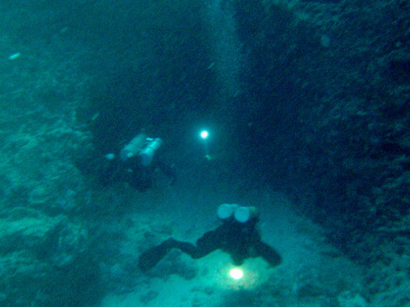 "Expert Cave divers (two tanks on backs) enter the ""Temple of Doom"" at 90' at the bottom of the Blue Holes. The Temple of Doom derives its name from divers and turtles that have perished in the cave's labyrinth."