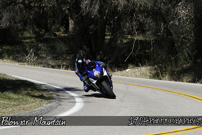 A suzuki GSX-R motorcycle Rider heads down south grade road on Palomar Mountain.