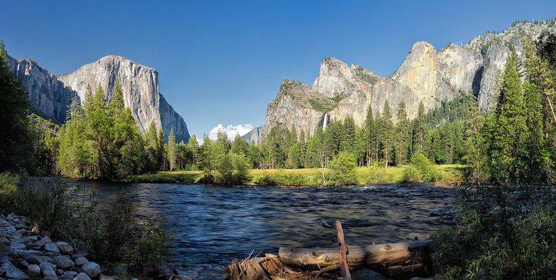 Yosemite Valley and the Merced River. This location is known as Valley View. To the right, Bridalveil Falls is almost covered by trees. To the left is El Capitan and at the  upper left is an unnamed waterfall appearing due to the heavy runoff.