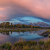Cotton candy colored clouds above the Tetons at sunrise. Panorama shot at Schwabacher Landing.