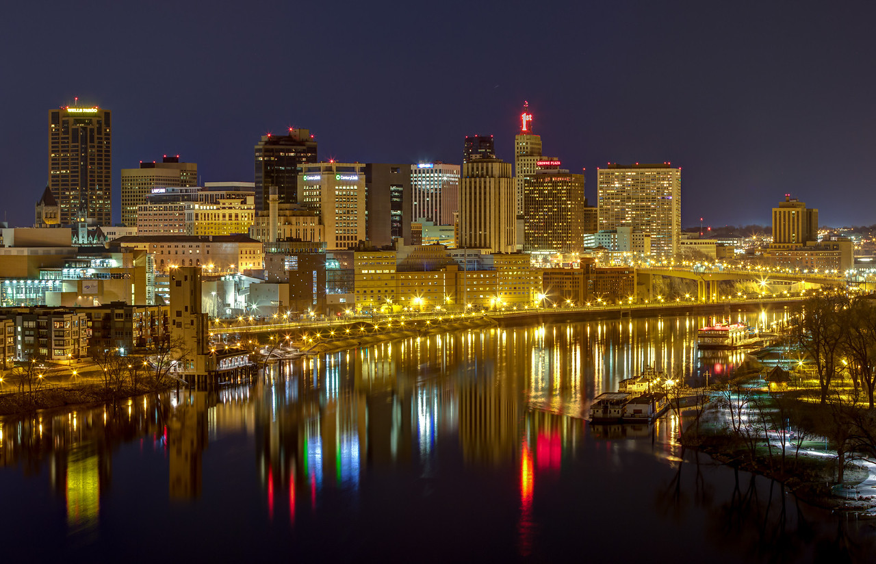 The night time skyline of Saint Paul reflected in the waters of the Mississippi river as seen in this panoramic image captured from the Smith Avenue high bridge.