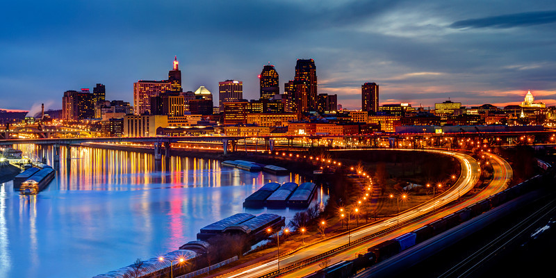 Saint Paul Night Skyline Reflections - The evening skyline of St. Paul, Minnesota is reflected in the Mississippi river as commuters make their way home and trains and barges park for the night in this panoramic image captured just after sunset on an autumn evening.