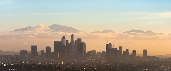Los Angeles skyline at sunrise with low fog and snow on San Gabriel Mountains