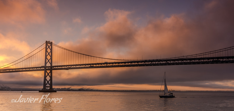 Bridge with sailboat at sunrise