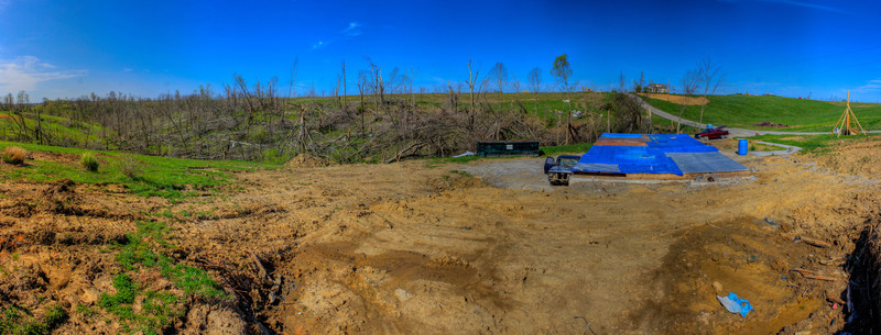 Tarp Foundation<br /> (Mar 27) Crittenden, Kentucky post the tornadoes.  I was working here doing a lot survey on this piece of property.  Trying to find and re-establish these peoples property corners.  They obviously lost everything but theis foundation.  Very tragic.<br /> <br /> I took this panoramic as a wide angle, as wide as I could get to show the extent of the damage.  The house is long gone and the forest of trees is desamated.  The next door neighbors house, which is behind this view (which is the view of my instrument for surveying) , you can not figure out where it even stood.  It must of a been a trailer that got completely lifted and torn apart.  No slab left to discern its old location.