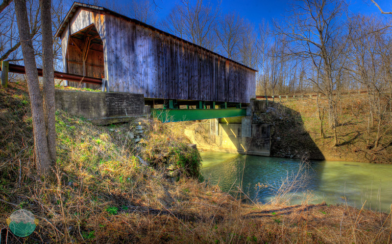 Hidden Gem<br /> This covered bridge is literally about 100 feet from Route 8 yet most people, myself included do not know that it exists.  It has been retro fitted obviously to keep the original bridge intact and a new bridge exists to take the load of the traffic.  You can still drive over it though if you wish.  It does have a low ton limit  but it is a nice little gem just below Route 8's busy traffic along the Ohio River.